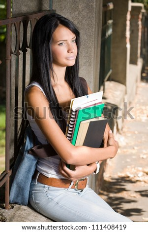 Portrait of an attractive young brunette student outdoors with exercise books. - stock photo