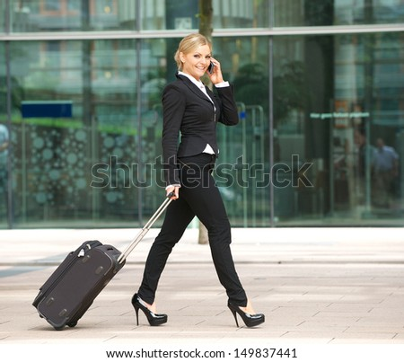 Portrait of an attractive young business woman walking and talking on phone in the city  - stock photo
