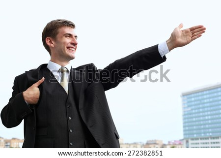 Portrait of an attractive young businessman in urban background wearing  suit a necktie. Blonde hair - stock photo