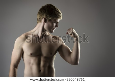 Portrait of an attractive young caucasian athlete is posing and flexing his muscles. The guy is shirtless and is wearing navy workout shorts. - stock photo