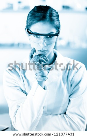 Portrait of an attractive, young, confident female health care professional in his working environment. Black and white, blue toned portrait. - stock photo
