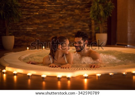 Portrait of an attractive young couple relaxing in a jacuzzi. High ISO image, ambiental light only. - stock photo