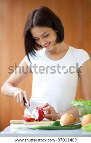 Portrait of an attractive young female cooking in the kitchen at home. Focus at the apple. - stock photo
