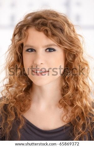 Portrait of an attractive young female front of window smiling.? - stock photo