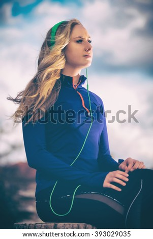Portrait of an attractive young female listening to music in green headphones. Filter applied - stock photo