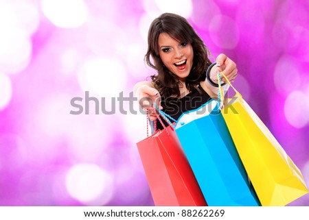 Portrait of an  attractive young girl with shopping bags in front of nice pink bokeh background - stock photo