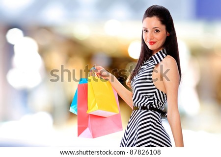 Portrait of an  attractive young girl with shopping bags in front of the shop