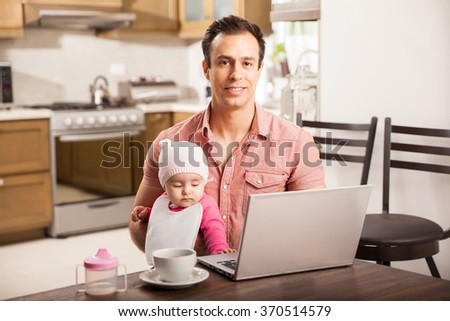 Portrait of an attractive young Hispanic father working on a laptop computer while looking after his baby daughter at home - stock photo