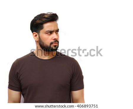 Portrait of an attractive young Indian man with beard looking away. - stock photo