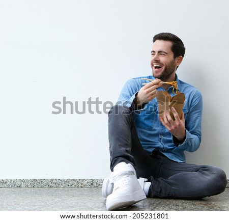 Portrait of an attractive  young man eating chinese food with chopsticks - stock photo