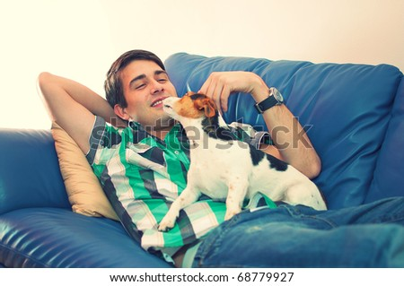 Portrait of an attractive young man playing with his cute dog lying on couch in his living room over white background - stock photo