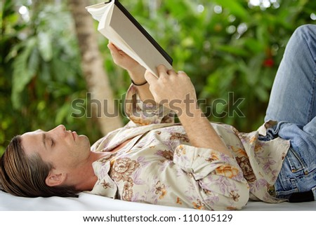 Portrait of an attractive young man reading a book and laying down on an outdoors bed in a tropical lush garden while on holiday. - stock photo