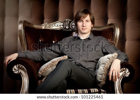 Portrait of an attractive young man sitting comfortably on armchair - stock photo