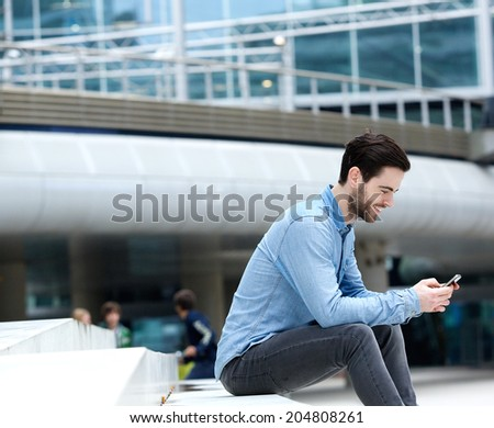 Portrait of an attractive young man sitting outdoors with mobile phone - stock photo
