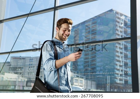 Portrait of an attractive young man walking and looking at mobile phone - stock photo