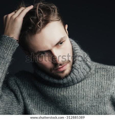 Portrait of an attractive young man with a beard in a warm sweater - stock photo