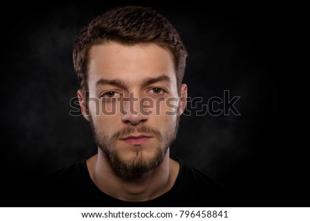 Portrait of an attractive young man with a beard on a dark background.
