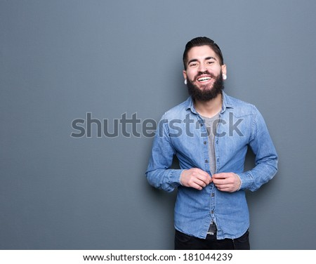 Portrait of an attractive young man with beard smiling and adjusting buttons on shirt  - stock photo