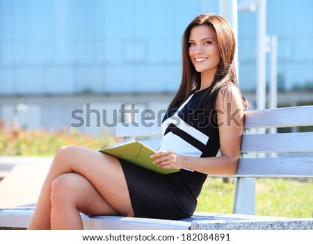Portrait of an attractive young professional woman sitting on a wooden bench in a park, smiling.  - stock photo