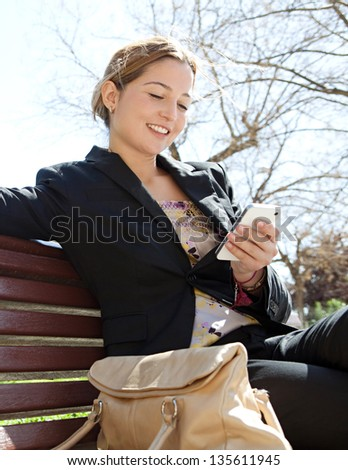 Portrait of an attractive young professional woman using a smartphone while sitting on a wooden bench in a park, smiling.