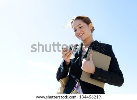 Portrait of an attractive young professional woman using a smartphone while standing against a sunny blue sky, smiling.
