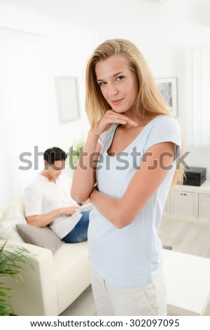 portrait of an attractive young woman at home with boyfriend in background