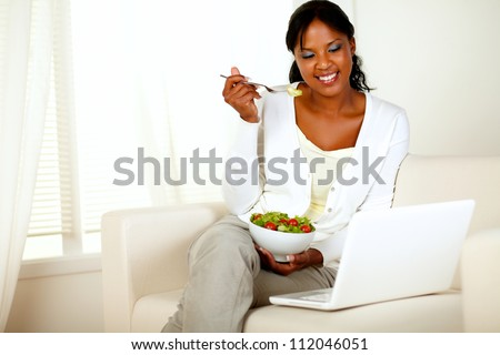 Portrait of an attractive young woman eating healthy salad while is sitting on couch in front of her laptop. with copyspace - stock photo