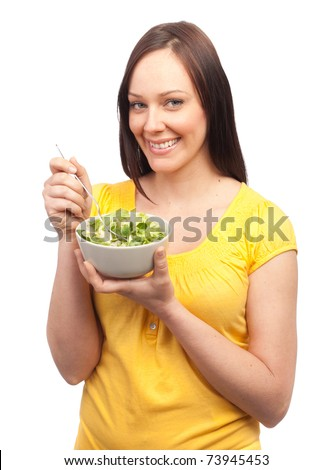 Portrait of an attractive young woman eating salad on white background