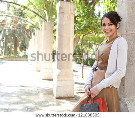 Portrait of an attractive young woman holding her shopping bags while leaning on a column in a romantic garden, outdoors. - stock photo