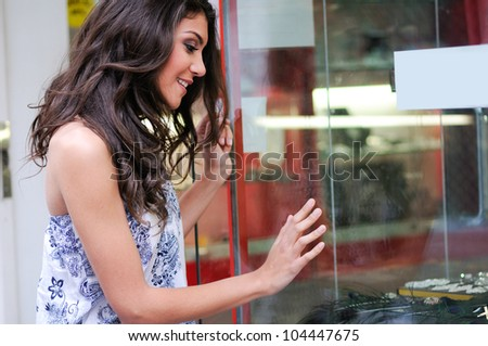 Portrait of an attractive young woman looking at the shop window