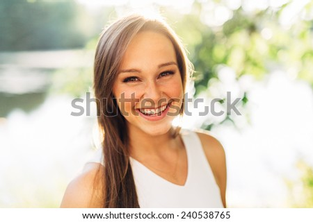Portrait of an Attractive Young Woman Looking right at camera smiling and laughing close up - stock photo
