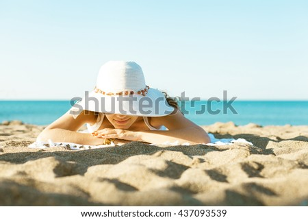 Portrait of an attractive young woman lying in the sun at the beach - stock photo