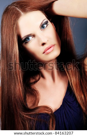 Portrait of an attractive young woman. Over grey background.
