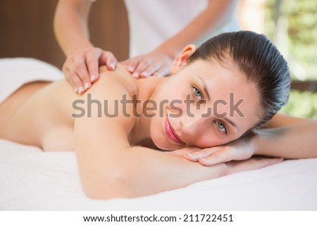 Portrait of an attractive young woman receiving back massage at spa center