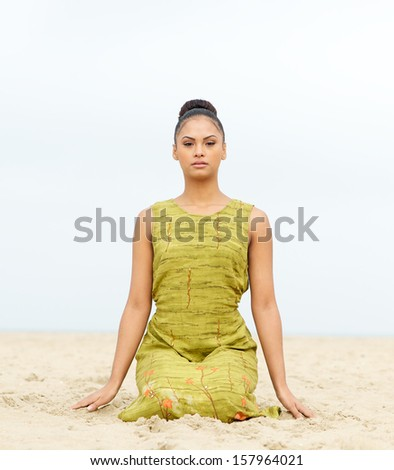 Portrait of an attractive young woman sitting alone  at the beach - stock photo