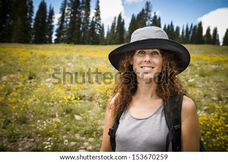 portrait of an attractive young woman standing in a mountain meadow - stock photo