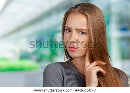 Portrait of an attractive young woman thinking deeply - stock photo