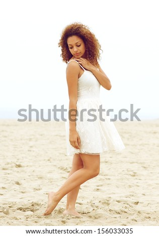 Portrait of an attractive young woman walking alone on beach  - stock photo
