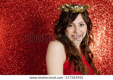Portrait of an attractive young woman wearing a gold stars crown while standing in front of a Christmas red glitter background. - stock photo