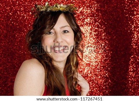 Portrait of an attractive young woman wearing a gold stars crown while standing in front of a Christmas red glitter background.