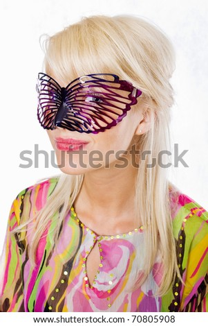 Portrait of an attractive young woman wearing carnival mask - stock photo