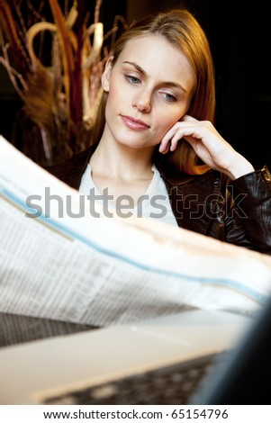portrait of an attractive young woman who reading newspaper - stock photo