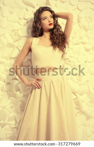 Portrait of an attractive young woman with beautiful curly hair over background of white paper flowers. Beauty, fashion. Cosmetics. - stock photo