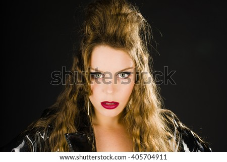 Portrait of an attractive young woman with long hair and a wild hairdo wearing a black shiny vinyl coat and very confidently looking at the camera.