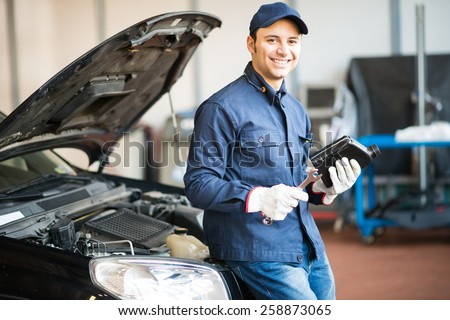 Portrait of an auto mechanic holding a jug of motor oil - stock photo