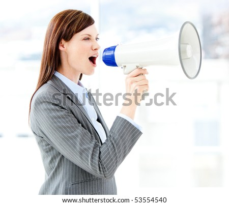 Portrait of an beautiful businesswoman using a megaphone in the office