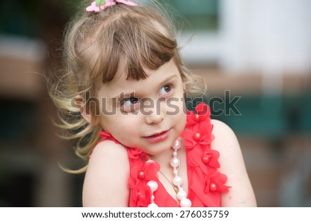 Portrait of an cheerful little girl in red dress.  - stock photo