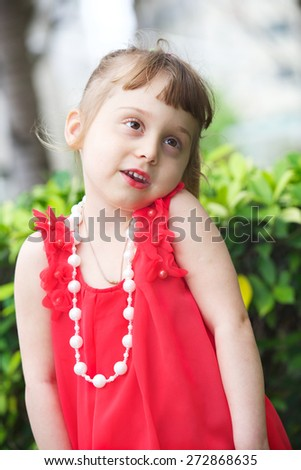 Portrait of an cheerful little girl in red dress. Vertical photo - stock photo