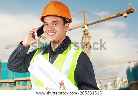 Portrait of an construction engineer holding blueprint conversation via phone with yellow crane and new building in the background - stock photo