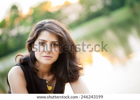 Portrait of an early 40s beautiful woman outdoors in summer by a lake - stock photo